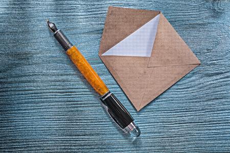 pluma de escribir antigua: Vintage post envelope with invitation fountain pen on wooden board.