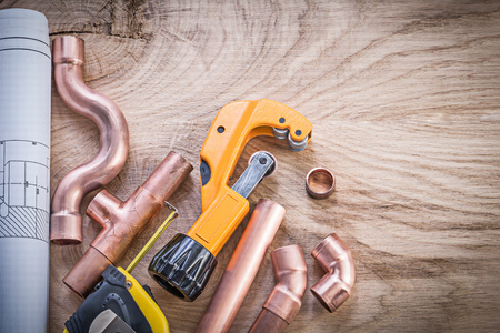 fixtures: Construction plans measuring tape water pipe cutter fixtures on wooden board plumbing concept.