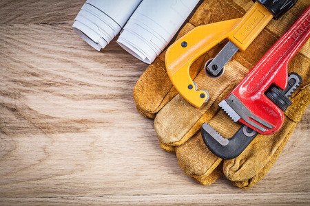 pipe wrench: Blueprints safety gloves pipe wrench cutter on wooden board plumbing concept. Stock Photo