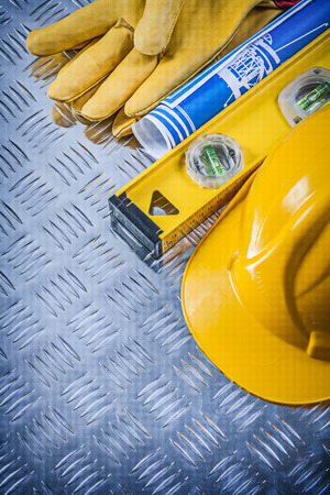 grooved: Blue blueprints hard hat safety gloves construction level on grooved metal plate. Stock Photo