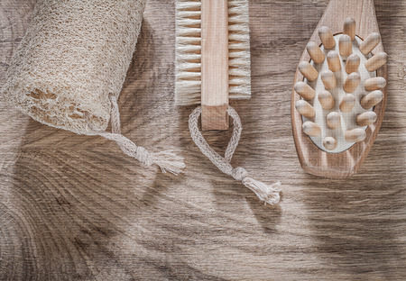 scrubbing: Composition of scrubbing loofah massager bath brush on wooden board spa treatment concept.
