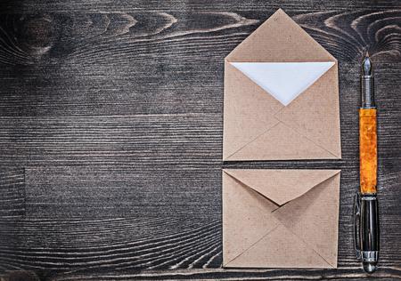 pluma de escribir antigua: Composition of vintage post envelopes fountain pen on wooden board copy space.