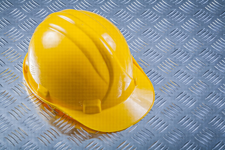Hard hat on grooved metal plate construction concept.