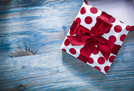 Red gift box with present on wooden board holidays concept.