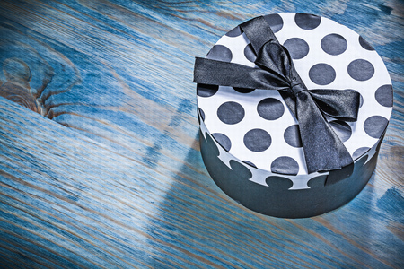 Round present box with blue ribbon on wooden board holidays concept. Stock Photo
