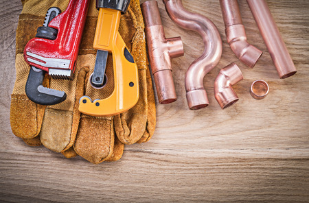 Protective gloves monkey wrench pipe cutter fixtures on wooden board plumbing concept.