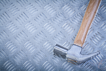 channeled: Claw hammer on grooved metal sheet top view construction concept.