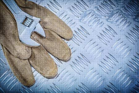channeled: Leather safety gloves adjustable spanner on channeled metal sheet construction concept.