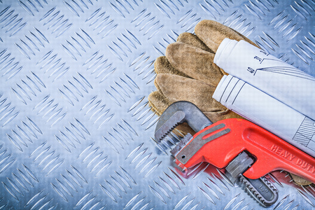 pipe wrench: Pipe wrench engineering drawings leather safety gloves on fluted metal plate construction concept. Stock Photo