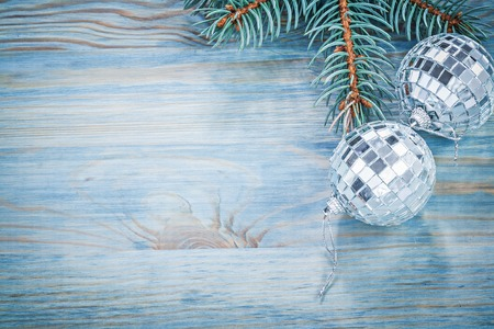 fir branch: Christmas mirror baubles fir branch on wooden board copy space holidays concept.