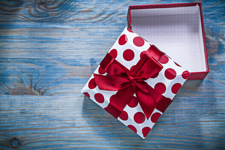 Red gift box with tied bow on wooden board holidays concept.