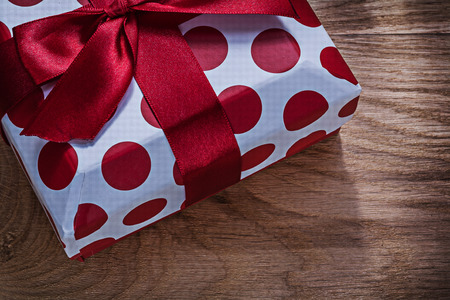 Red present box on wooden board close up view celebrations concept.