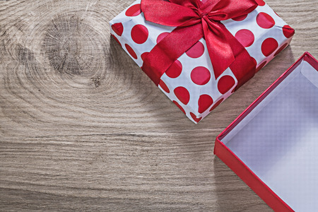 Red wrapped present box with tape on wooden board celebrations concept.