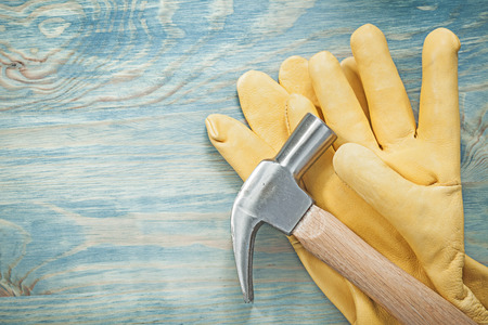 claw hammer: Claw hammer leather safety gloves on wood board construction concept.