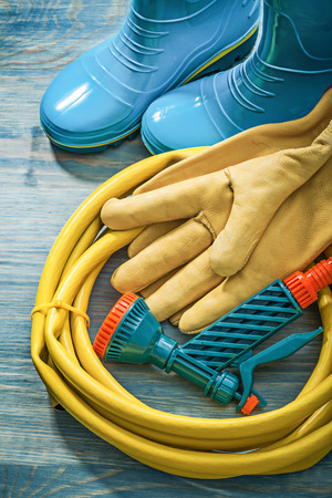 Rubber boots leather protective gloves garden hose on wooden board gardening concept. Stock Photo