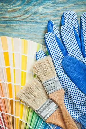 repaint: Protective gloves color palette paintbrushes on wooden board construction concept.
