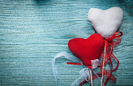 festal: White red hearts with ribbons on wooden board holidays concept.