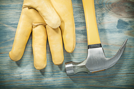 claw hammer: Horizontal version of claw hammer leather safety glove on wooden board construction concept.