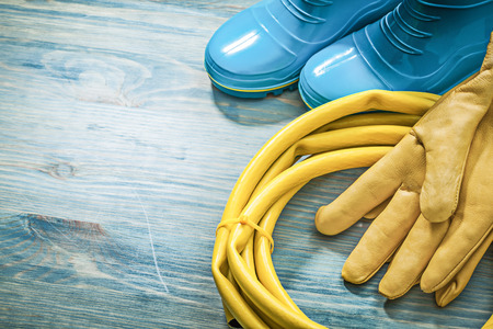 Rubber boots leather safety gloves garden hose on wooden board gardening concept. Stock Photo