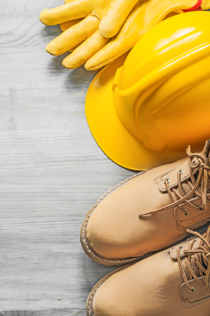 Waterproof lace boots hard hat protective gloves on wooden board construction concept.