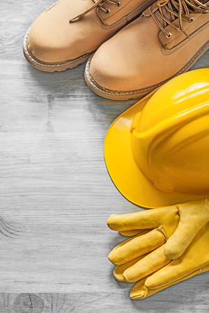 Lace boots hard hat leather protective gloves on wooden board construction concept.