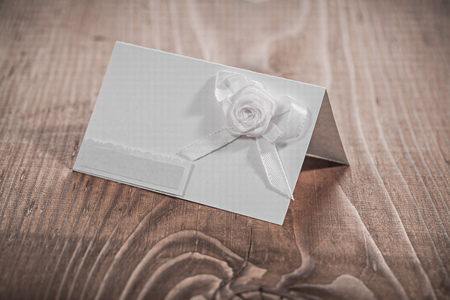 closed ribbon: white invitation card with flowers.