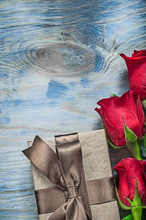 Composition of wrapped gift box red roses on wooden board celebrations concept.