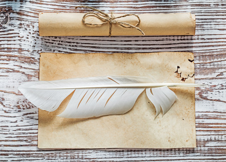 corded: Old blank sheet corded paper rolls quill on vintage wooden board.