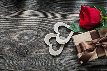 Wooden hearts red rose gift box on wood board celebrations concept. Stock Photo