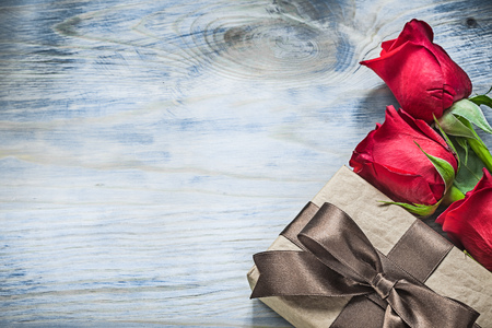 Set of wrapped present box red roses on wooden board celebrations concept.