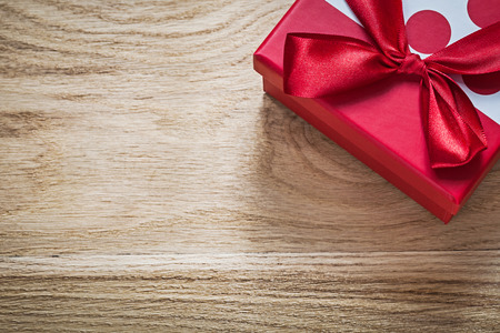 Gift box with red bow on wooden board celebrations concept.