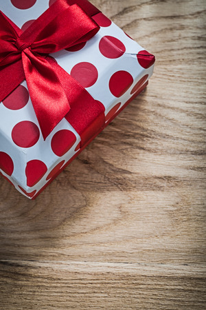 Present box with red bow on wooden board holidays concept.
