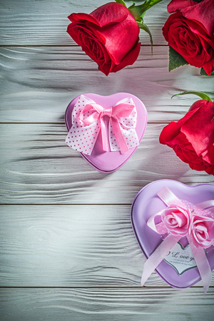 Heart-shaped metal present boxes natural red roses on wooden board holidays concept.