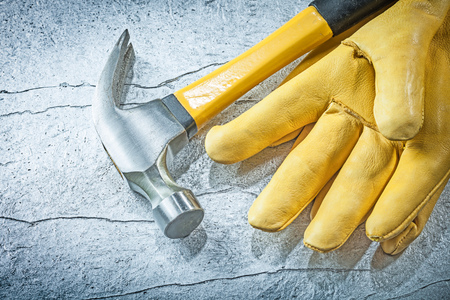 claw hammer: Leather protective gloves claw hammer on metallic background construction concept.