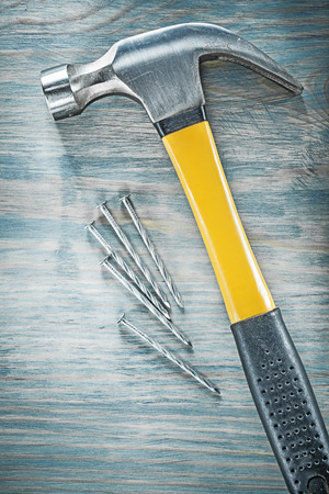 Assortment of claw hammer nails on wooden board construction concept. Stock Photo