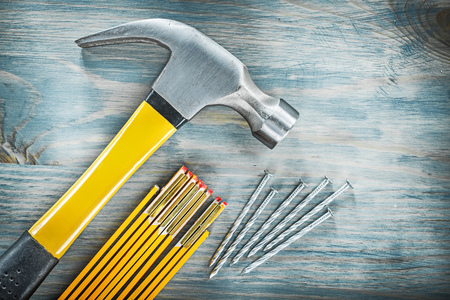Claw hammer pile of nails wooden meter on wood board construction concept. Stock Photo