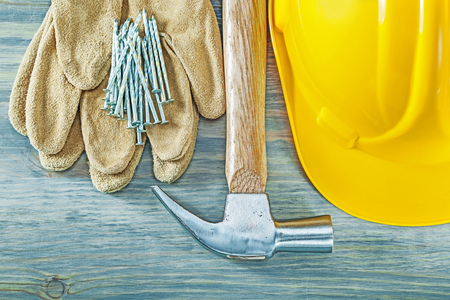 claw hammer: Hard hat protective gloves claw hammer nails on wooden board construction concept.