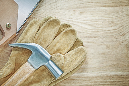 Claw hammer protective gloves stainless handsaw on wooden board construction concept. Stock Photo