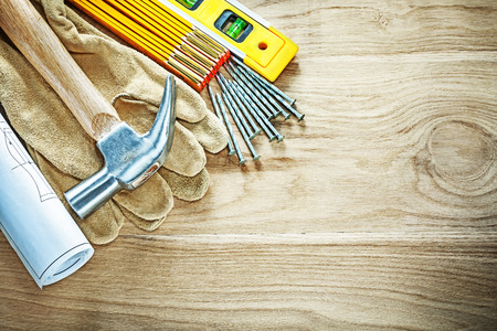 claw hammer: Engineering drawings construction level protective gloves wooden meter claw hammer nails on wood board.