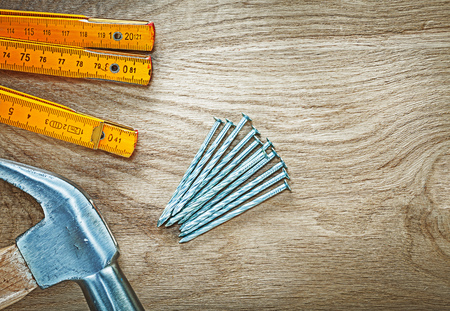 Horizontal image of claw hammer wooden meter construction nails on wood board building concept.