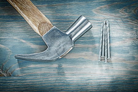 Set of claw hammer nails on vintage wooden board construction concept. Stock Photo