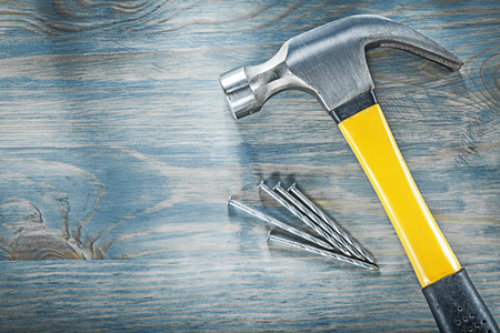 Composition of claw hammer stainless nails on wooden board construction concept.