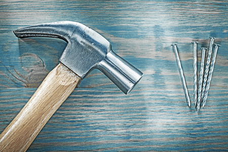 Horizontal view of claw hammer nails on wooden board construction concept.