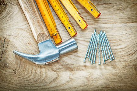 Composition of claw hammer wooden meter stainless nails on wood board building concept.