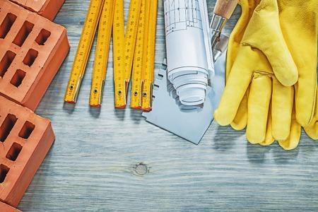 Rode bakstenen leer beschermende handschoenen houten meter bouw tekeningen metselen Troffel bouwconcept.