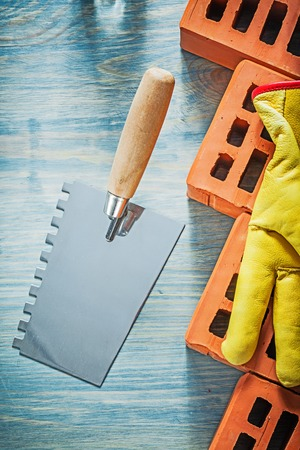 palette knife: Palette knife red bricks safety gloves on wood board bricklaying concept. Stock Photo