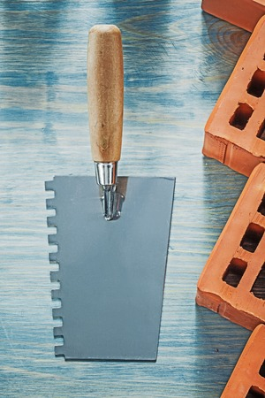 palette knife: Plastering trowel red bricks on wood board bricklaying concept.
