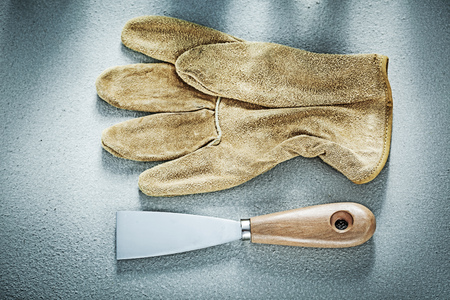 palette knife: Putty knife leather protective gloves on concrete background construction concept. Stock Photo