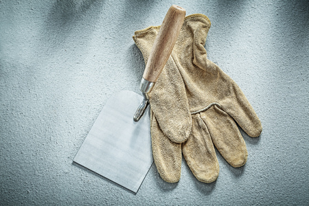 palette knife: Stainless putty knife leather protective glove on concrete background construction concept.