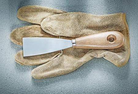 palette knife: Palette knife leather protective gloves on concrete surface construction concept.